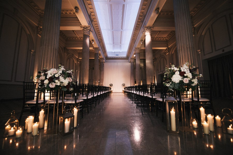 inside of the treasury on the plaza setup for wedding reception, with flowers and candles, tall pillars, and more