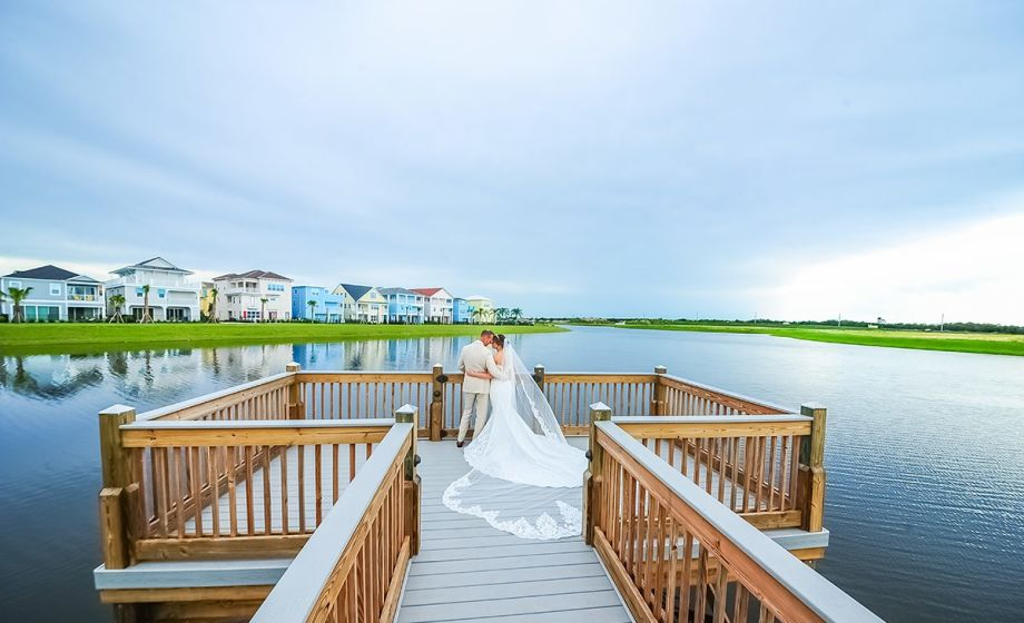 bride and groom hugging on the end of a dock looking out over the water