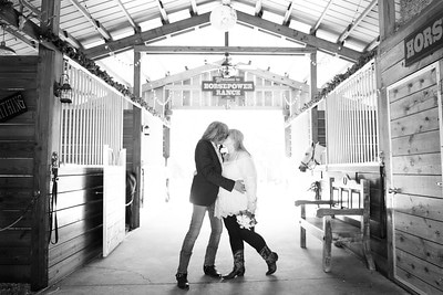 black and white photo of couple kissing in barn with horses in background