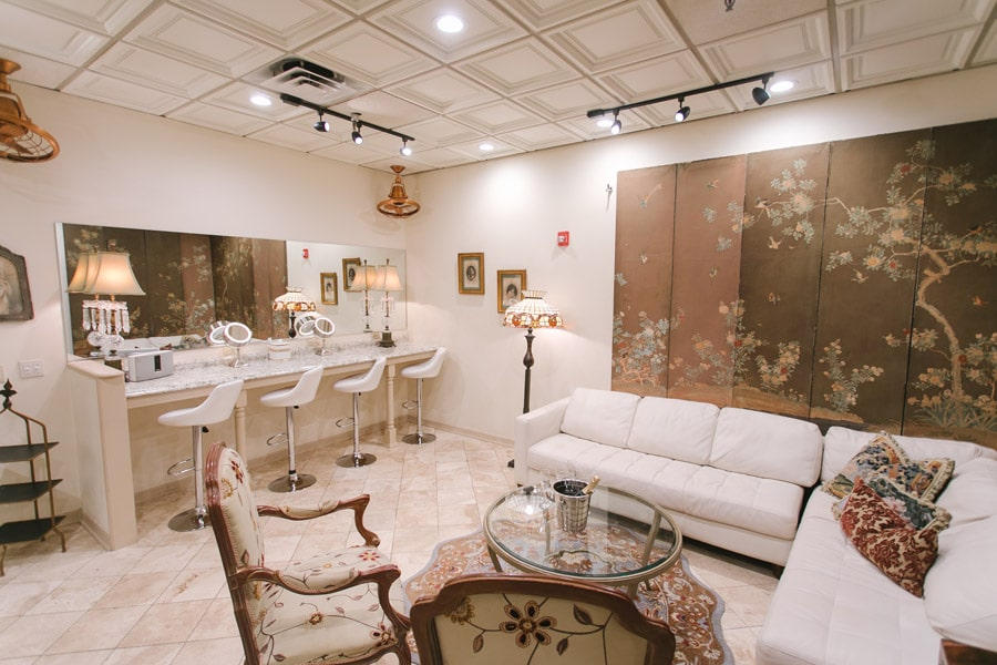 area for the bride and her bridesmaids to get ready, with large mirrors, plenty of light, and large white couch