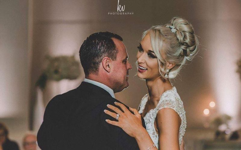 bride smiling during first dance at wedding reception with her hair and makeup provided by About Face Design Team