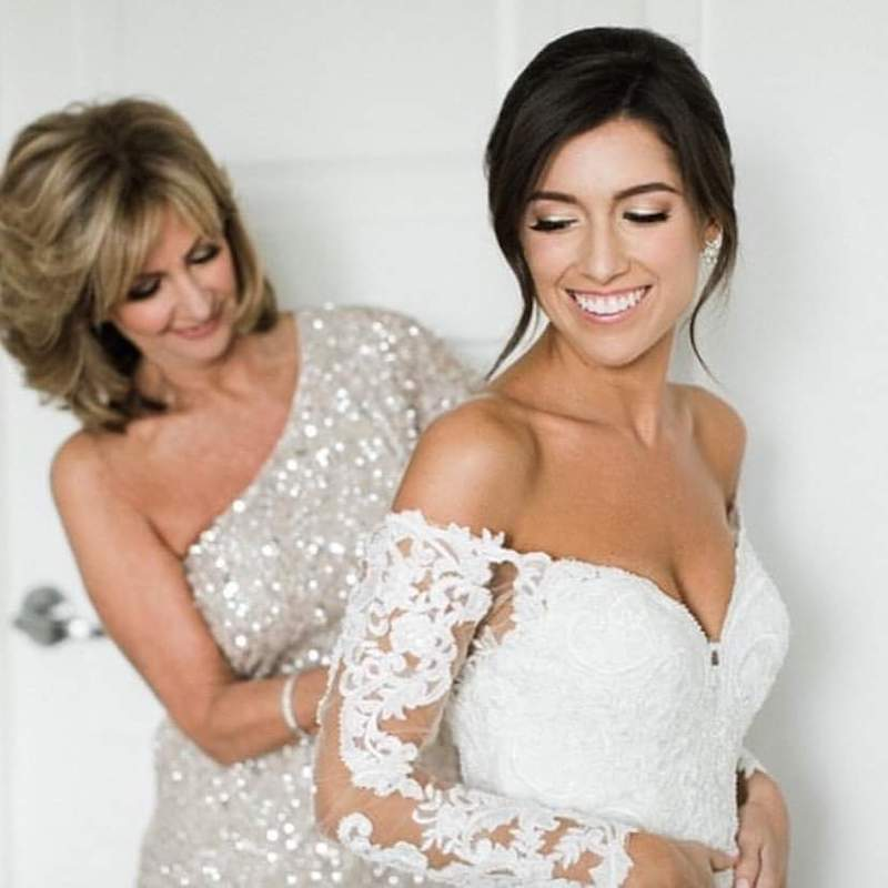 bride smiles as her mother zips up her dress from the back