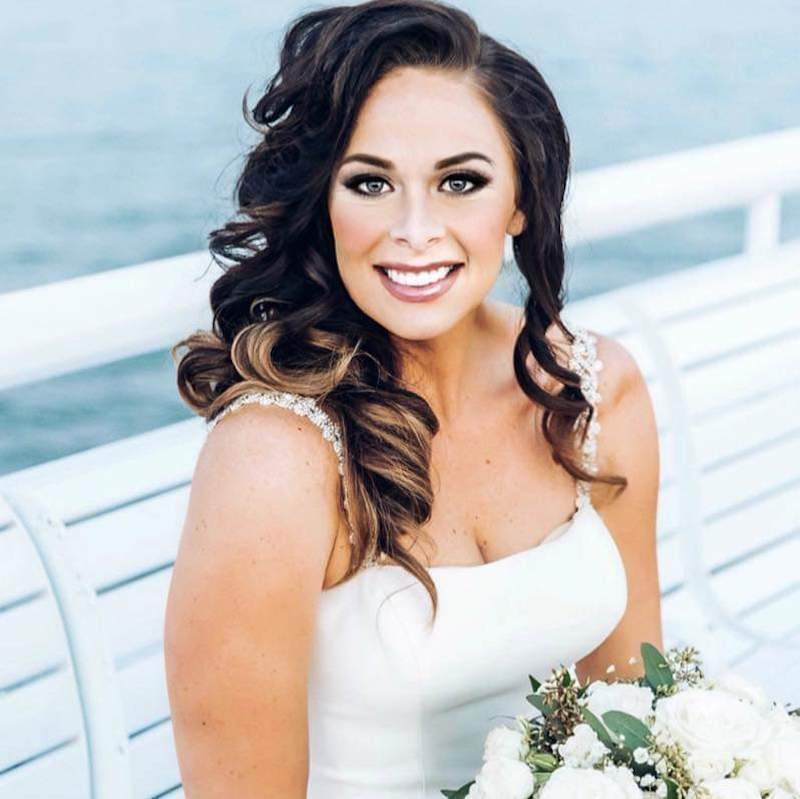 bride smiling while sitting on bench near the water in full hair and makeup provided by About Face Design Team