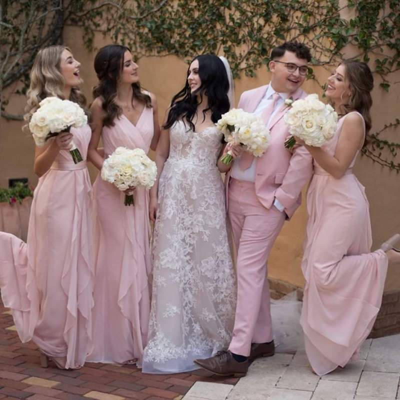 bride smiling with her bridesmaids while standing in an outdoor courtyard