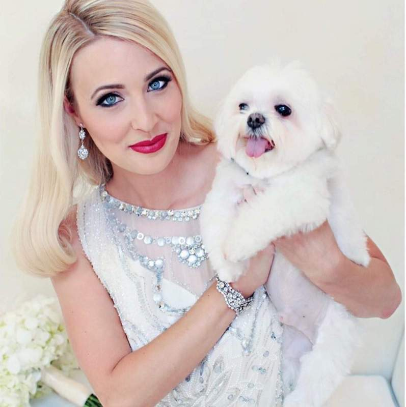 bride holding her puppy while in full hair and makeup provided by About Face Design Team