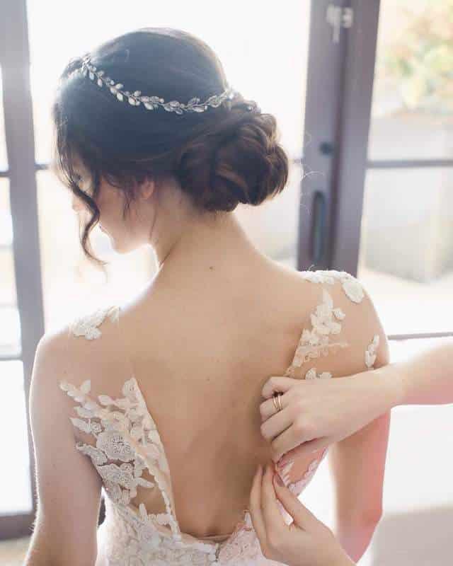 bride getting helped into her wedding dress