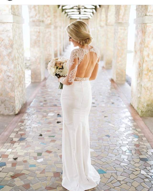 bride standing in covered walkway while looking at her flower bouquet
