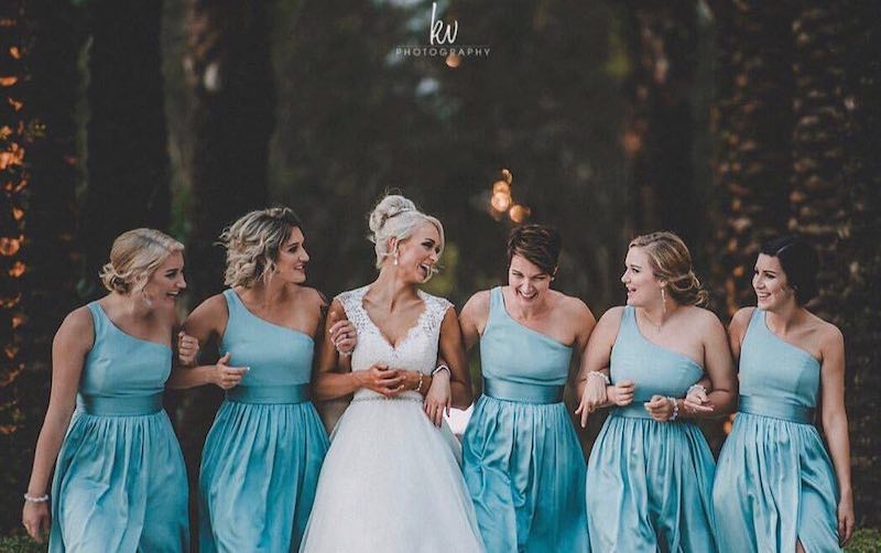 bride linking arms with her bridesmaids who are all in matching blue dresses