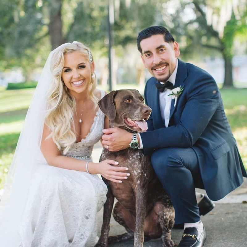 bride in full hair and makeup kneeling next to her groom with their dog in between