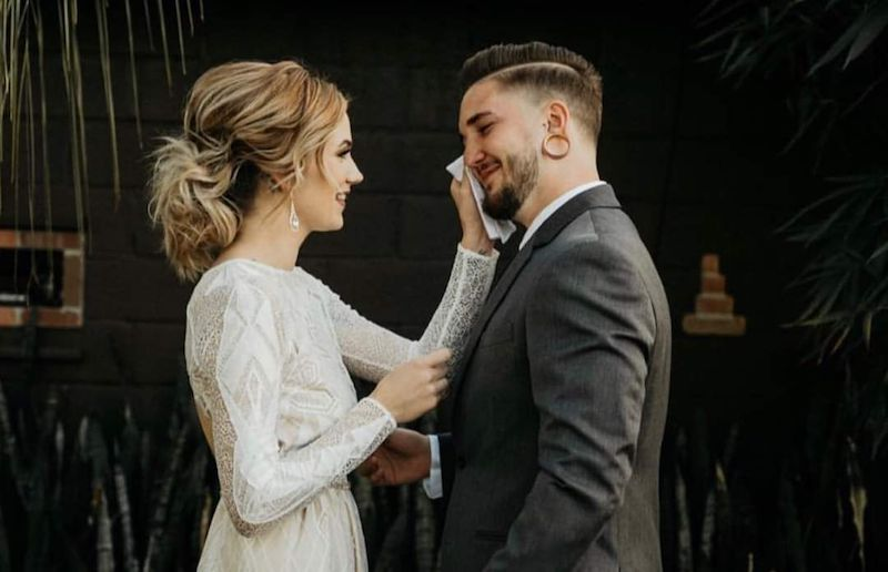 bride brushes away a tear from her groom