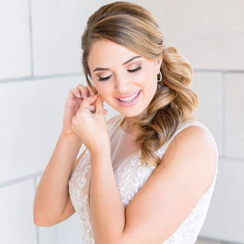bride putting on her earrings while in full hair and makeup provided by About Face Design Team