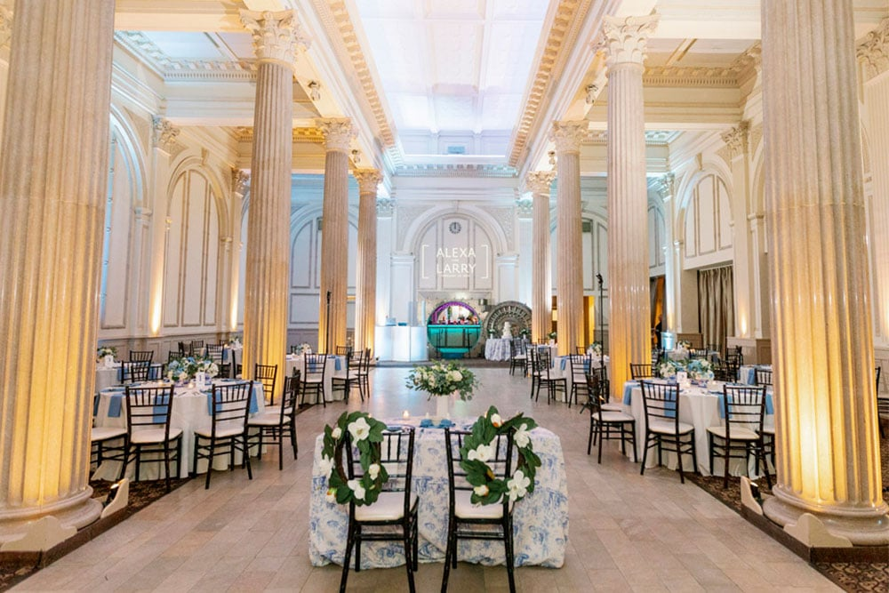 wedding reception area at the treasury on the plaza with white and blue linens, and a lot of white and yellow light