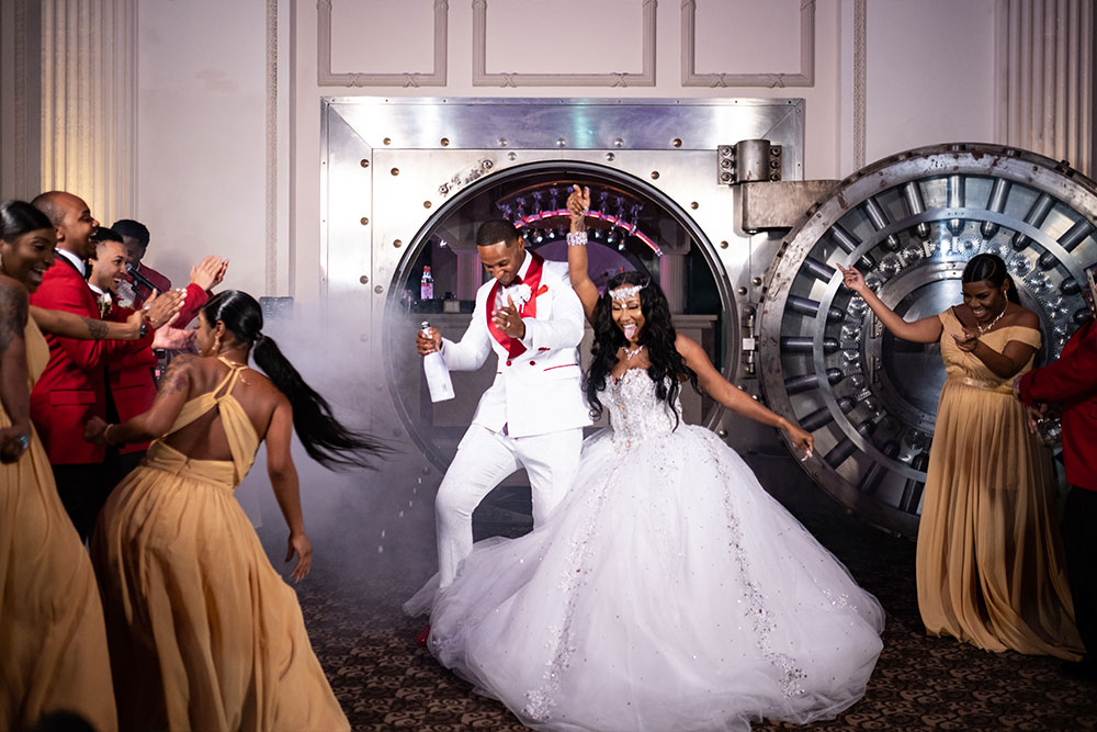bride and groom dancing as they exit the vault at the treasury on the plaza to enter their wedding reception