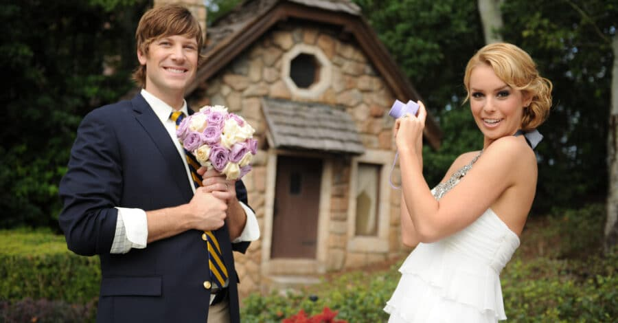bride takes a picture of her husband holding her flower bouquet