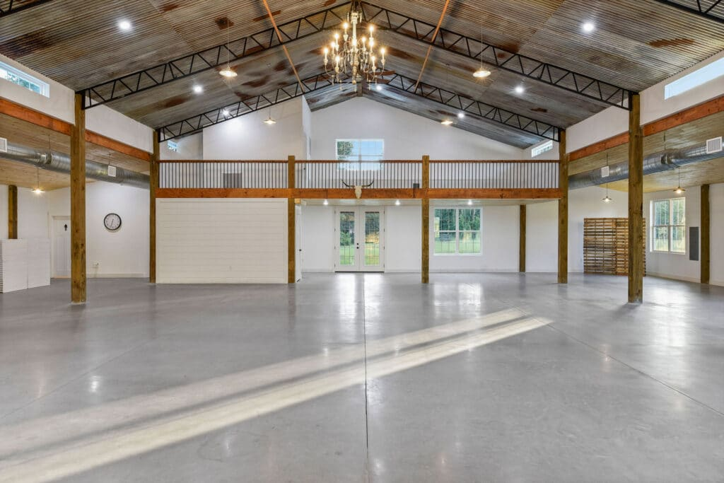interior of white barn event space with wood rafters and beautiful chandeliers