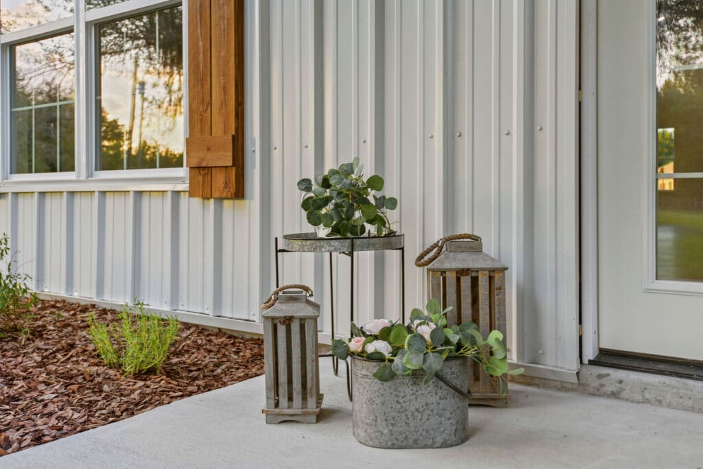 assortment of potted plants and lanterns at front entrance to white barn