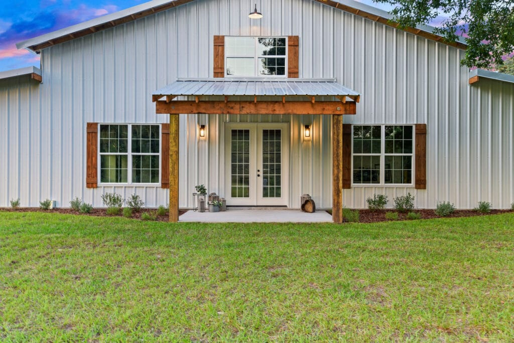 white barn with brown shutters and entryway at sunset