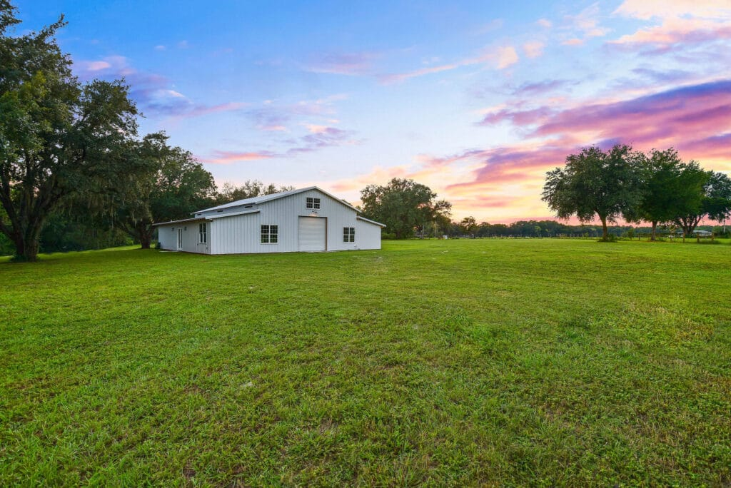 white barn event venue in large green field with beautiful clouds and sunset behind it