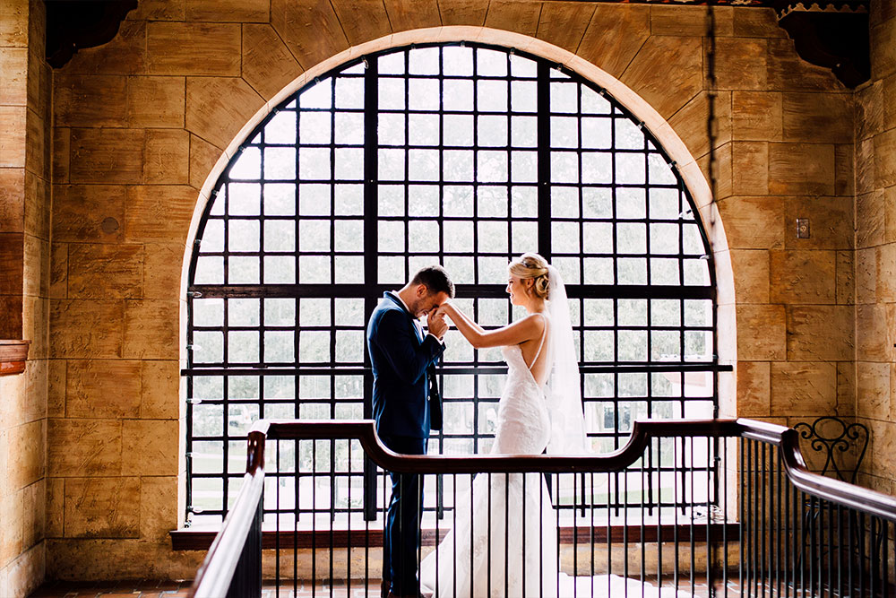 bride and groom holding hands while standing in front of large window at the treasury on the plaza