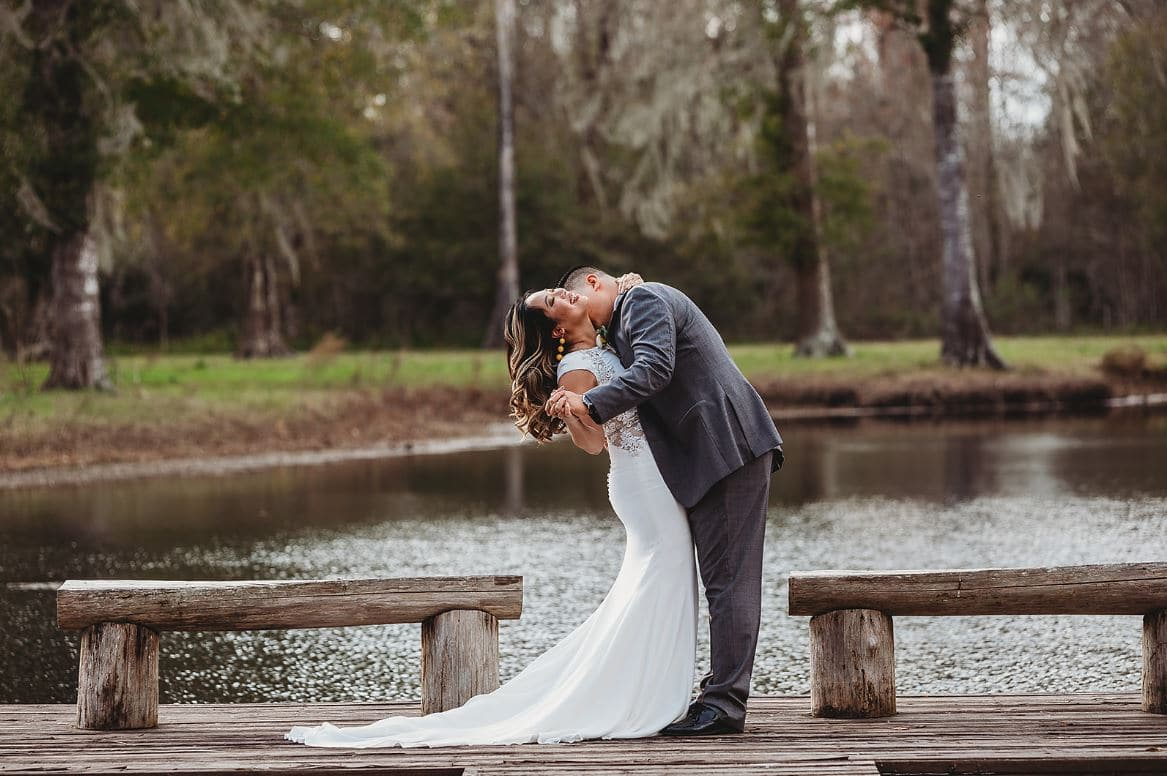 groom kissing bride overlooking water