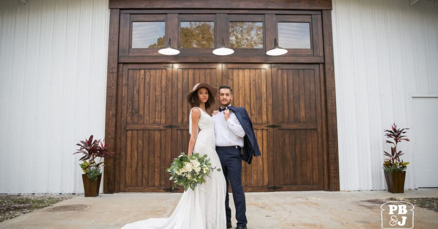 bride and groom standing in front of large dark wooden doors at Cypress Creek Farmhouse