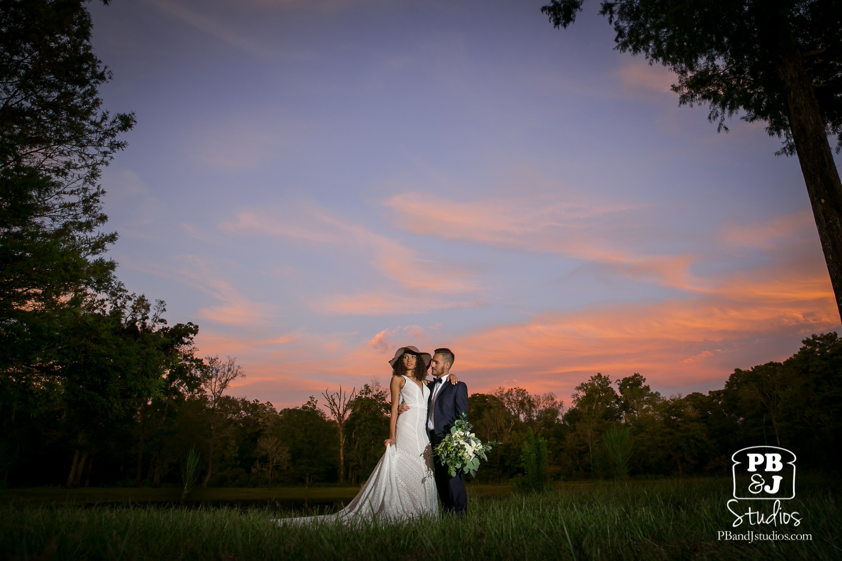 couple outside in field at sunset