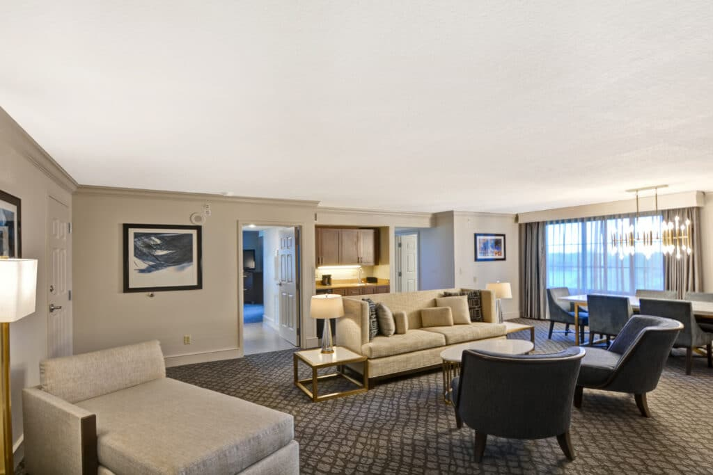 large hotel suite with white sofa, blue chairs, dining table, and chandelier
