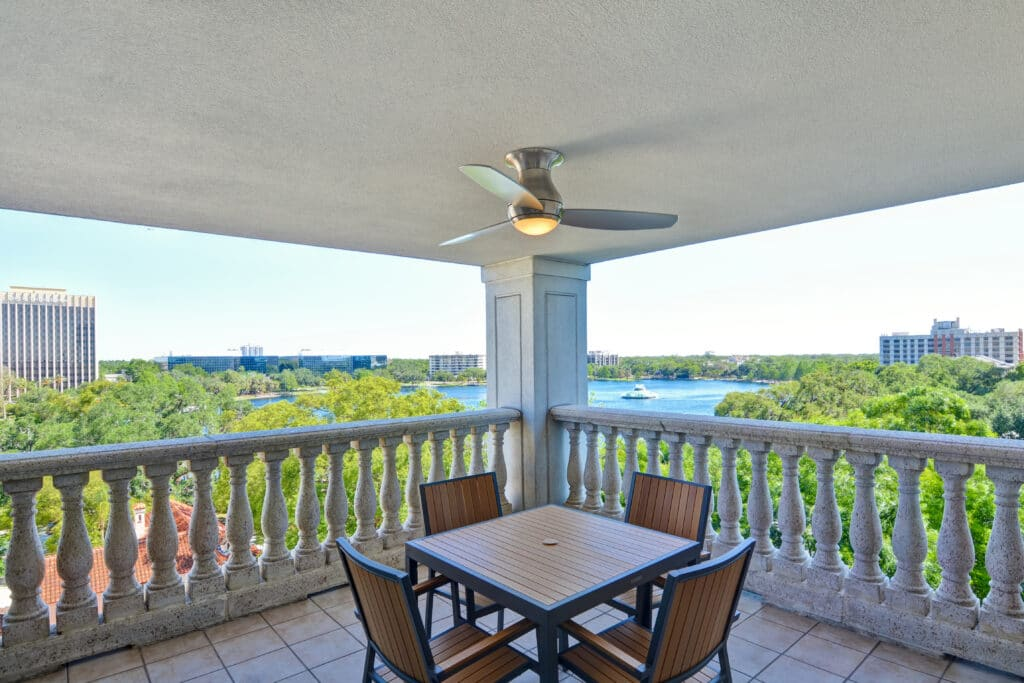 large corner balcony with square table, chairs, and ceiling fan overlooking a lake