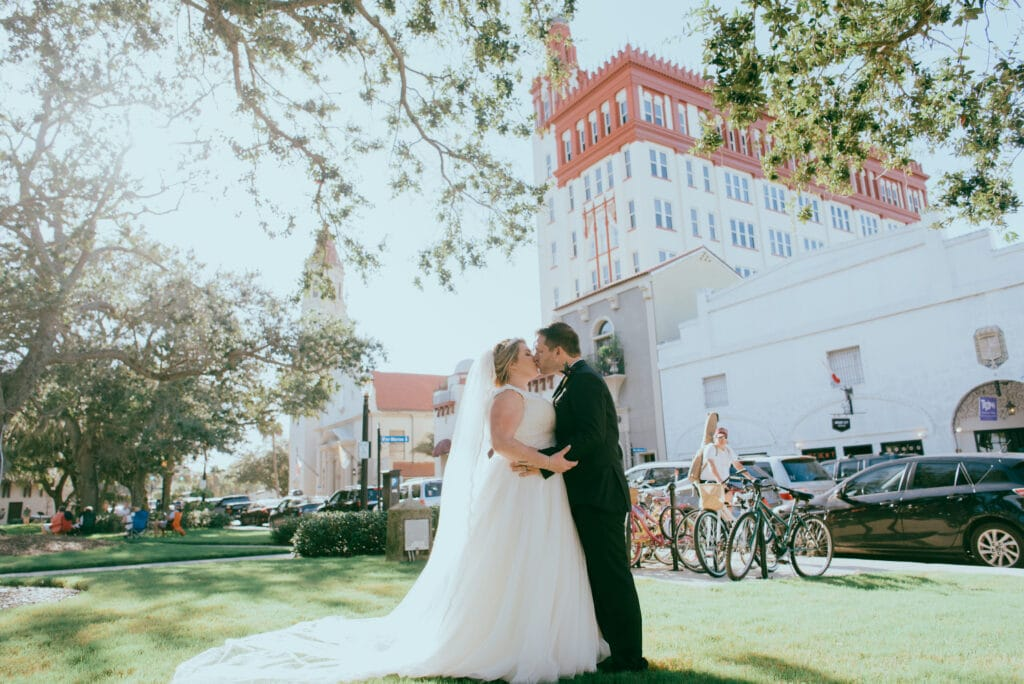 bride and groom kissing under tree on sunny day