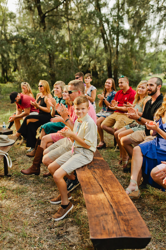 guests clapping during wedding ceremony while sitting on dark wood benches