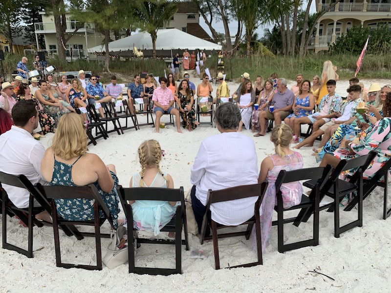 guests sitting in chairs set up in spiral formation on the beach waiting for the bride and groom to arrive