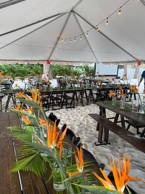 tent set up on the beach for outdoor wedding reception, with dark wood tables and chairs