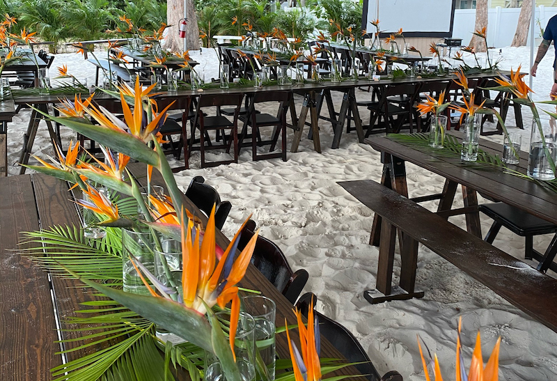 wedding reception area set up on the beach with matching dark wood tables and chairs