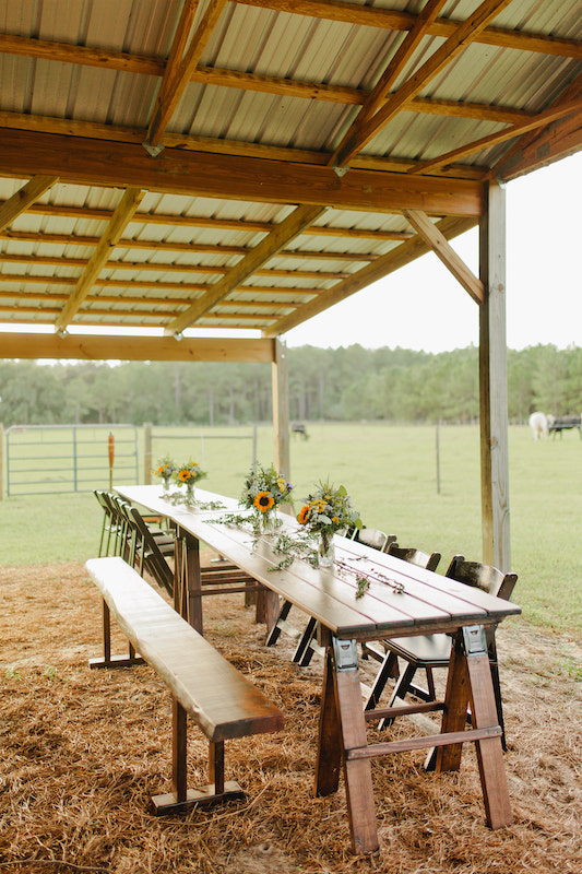 long tables, benches, and chairs set up for guests at a wedding reception on a farm