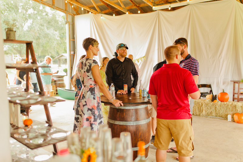 guests drinking and having fun while standing around a table made from a dark wood barrel