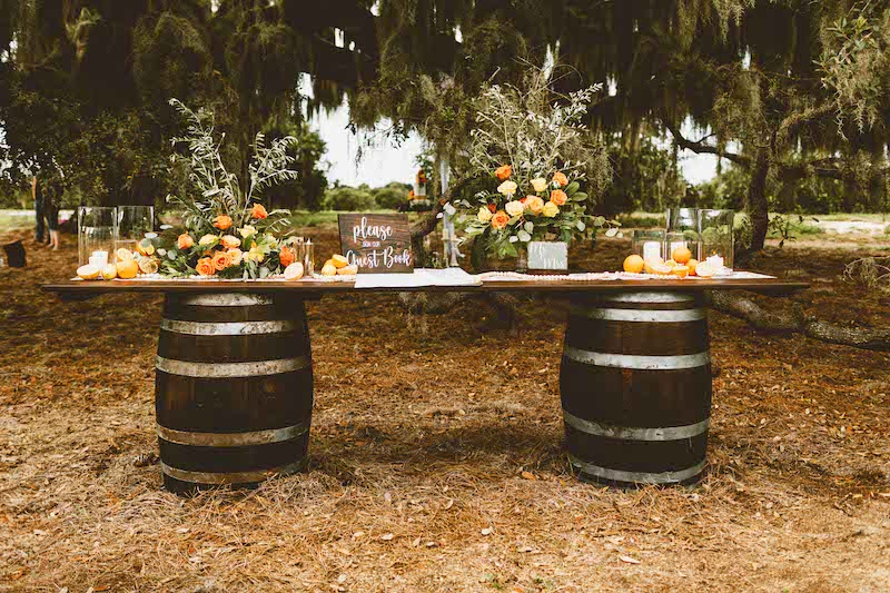 guestbook table made from dark wood and two wooden barrles