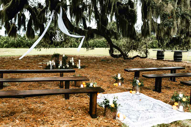 dark wood benches set up for outdoor wedding ceremony, with candles, flowers, and a carpet used as decoration