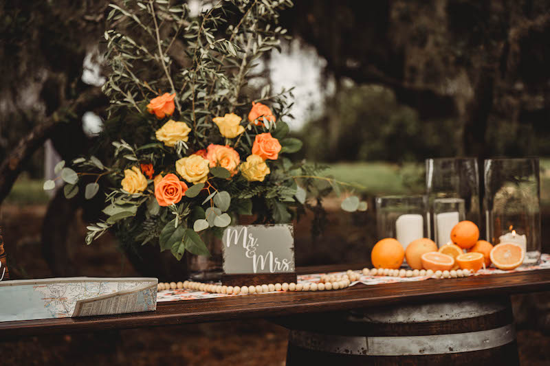 table for decorations at wedding made from dark wood and two wood barrels