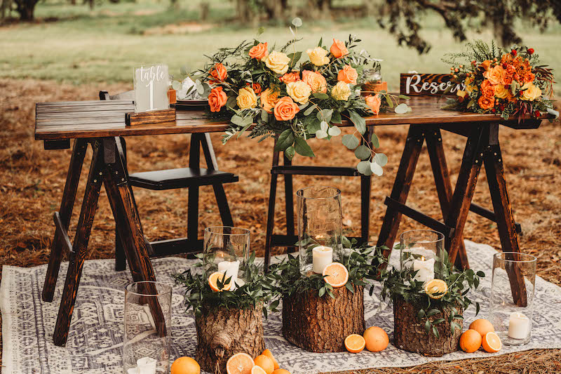 sweetheart table used for outdoor wedding reception made of dark wood and decorated with flowers and candles