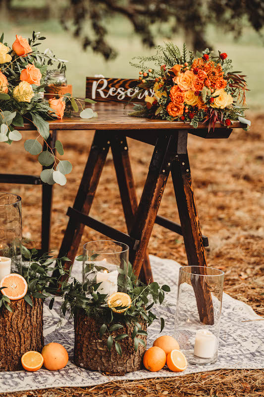 sweetheart table for wedding reception decorated with yellow and orange flowers, actual oranges, and candles