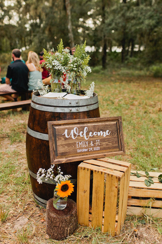 welcome sign to Emily and JT's wedding, propped up on crates and leaning against a decorated dark wood barrel