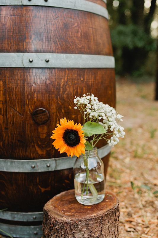 a small sunflower sitting in a glass jar on a wooden stump in front of dark wood barrel