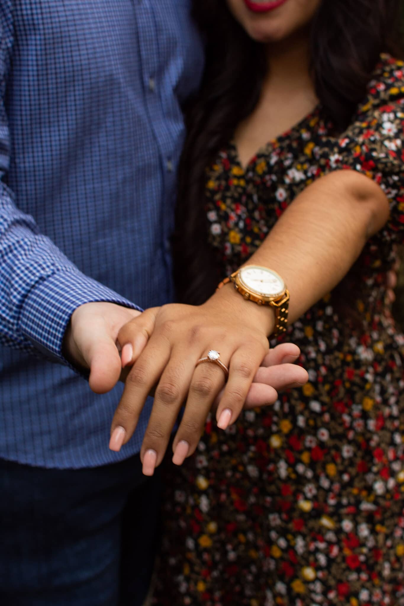 engaged couple stands together and man holds out fiances hand with new engagement ring on it and pink nails