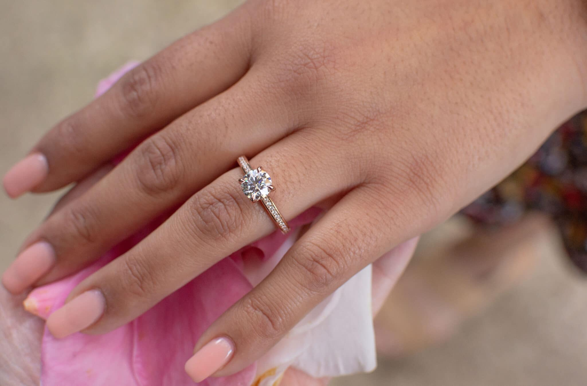close up image of woman's hand with light pink colored nails and engagement ring on