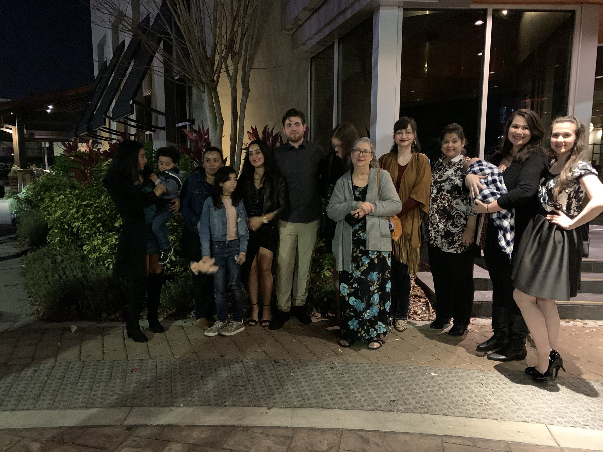 large family stands together for picture outside of building at night on sidewalk