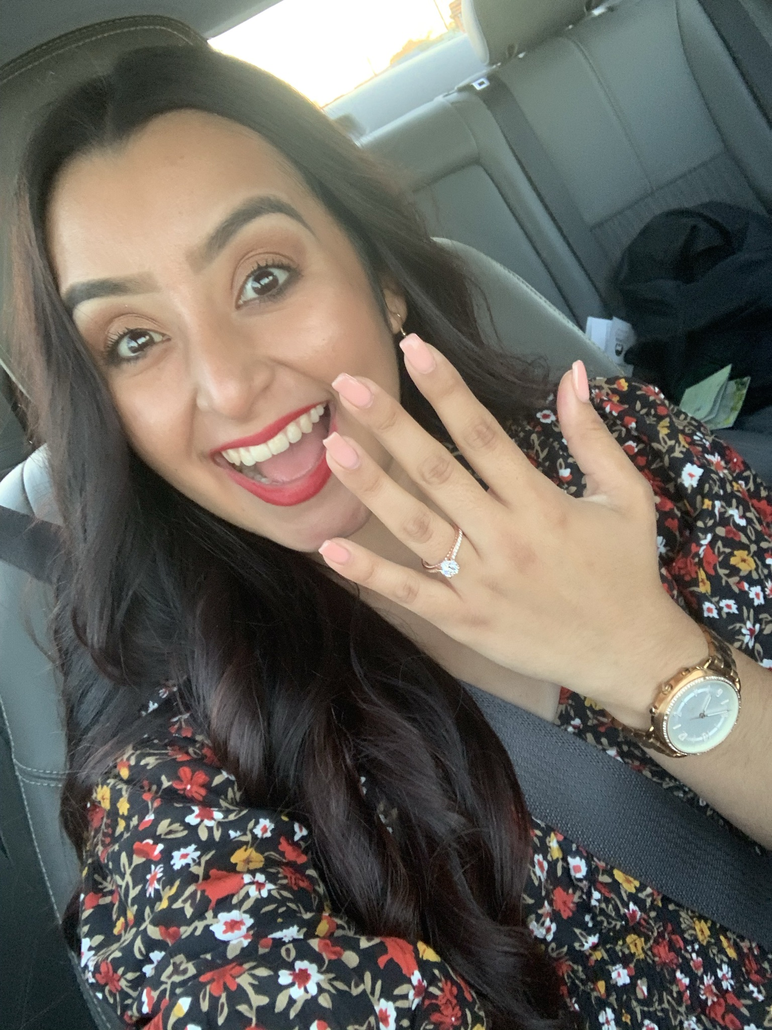 girl wearing floral dress red lipstick watch in the car smiles big while holding up hand with new engagement ring