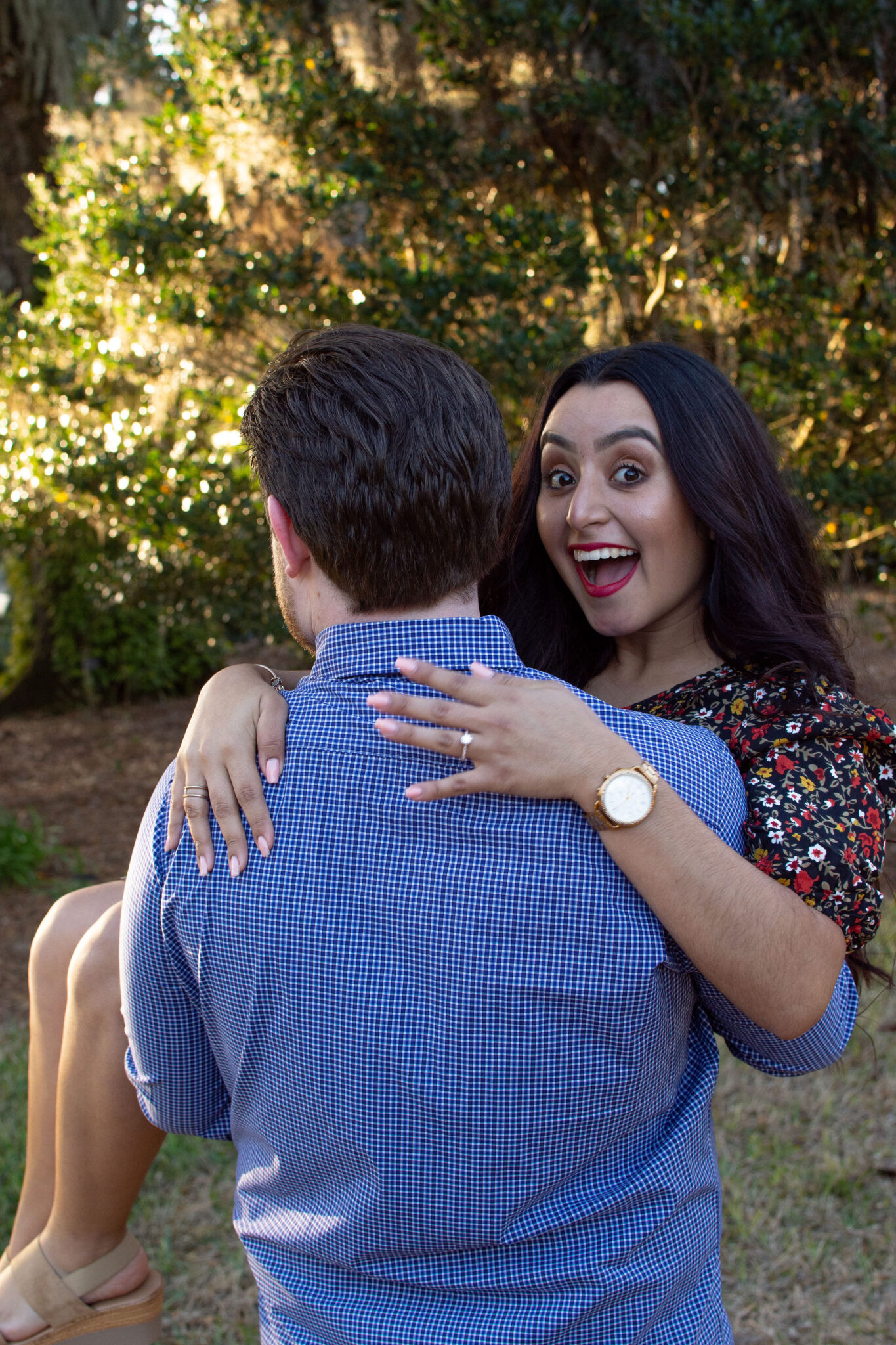 picture from behind man wearing blue long sleeve shirt holding his fiance while she smiles big showing off her engagement ring
