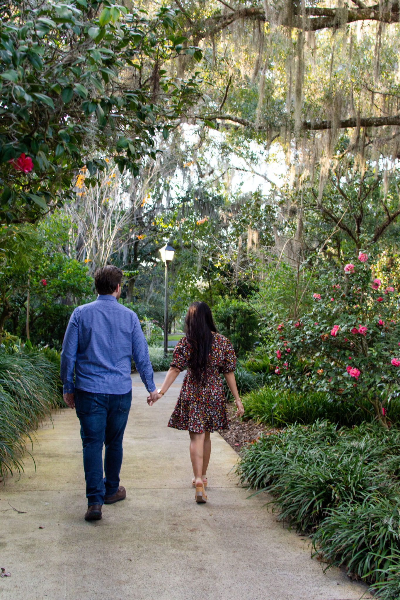 couple walks hand and hand together down a path outside at harry p leu gardens