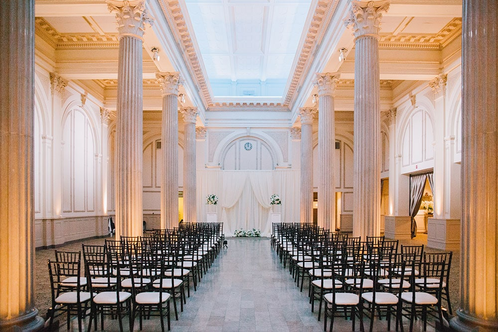 inside wedding reception area at the treasury on teh plaza, with nice chairs, tall pillars, and curtains