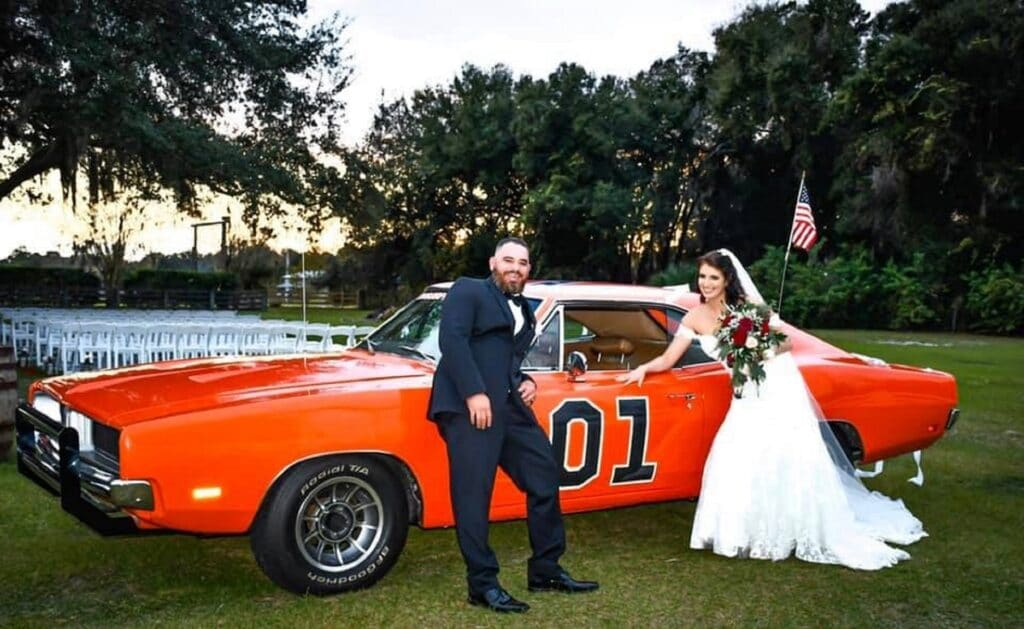 bride and groom leaning on orange sports car with number one on it